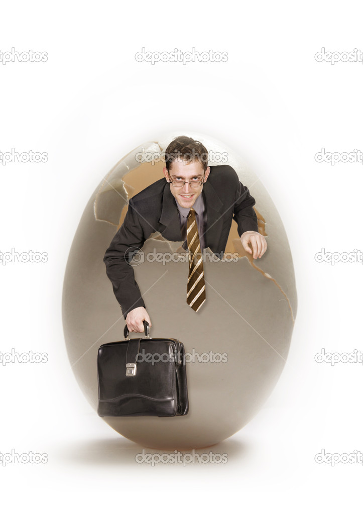 Young businessman looks out from big egg  Stock Photo #1523944