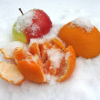 Apple and mandarin in the snow — Stock Photo
