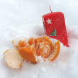 Mandarin and a red candle in the snow - Stock Photo