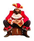 Pirate is sitting on the chest. Isolated on white. — Stock Photo