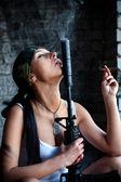 Mercenary with M4 submachine gun and big cigar is looking on the smoking muffler. — Stock Photo