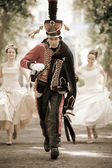 Pretty hussar in vintage outfit is escaping from brides. Retro-styled photo. — Stock Photo