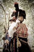 Duelling hussars on the garden background. Retro-styled photo. — Stock Photo