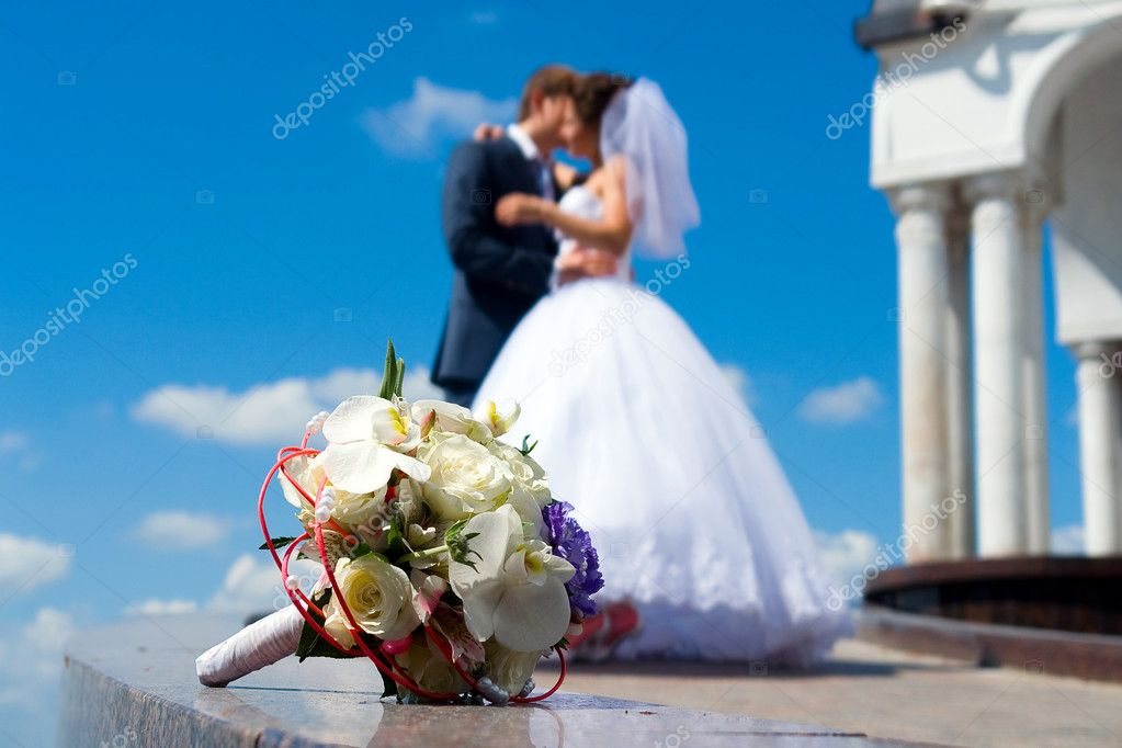 Bride's bouquet on the marble. Kissing couple on the background. — Stock Photo #1227631