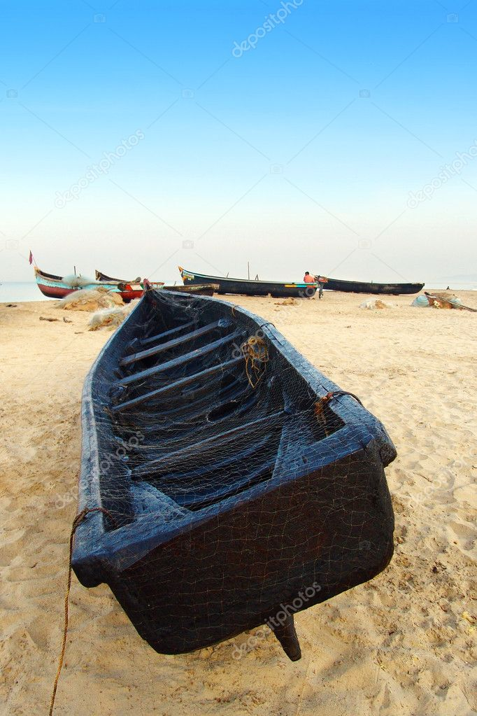 Indian boat laying on the beach covered with fishing net. — Stock Photo #1227707