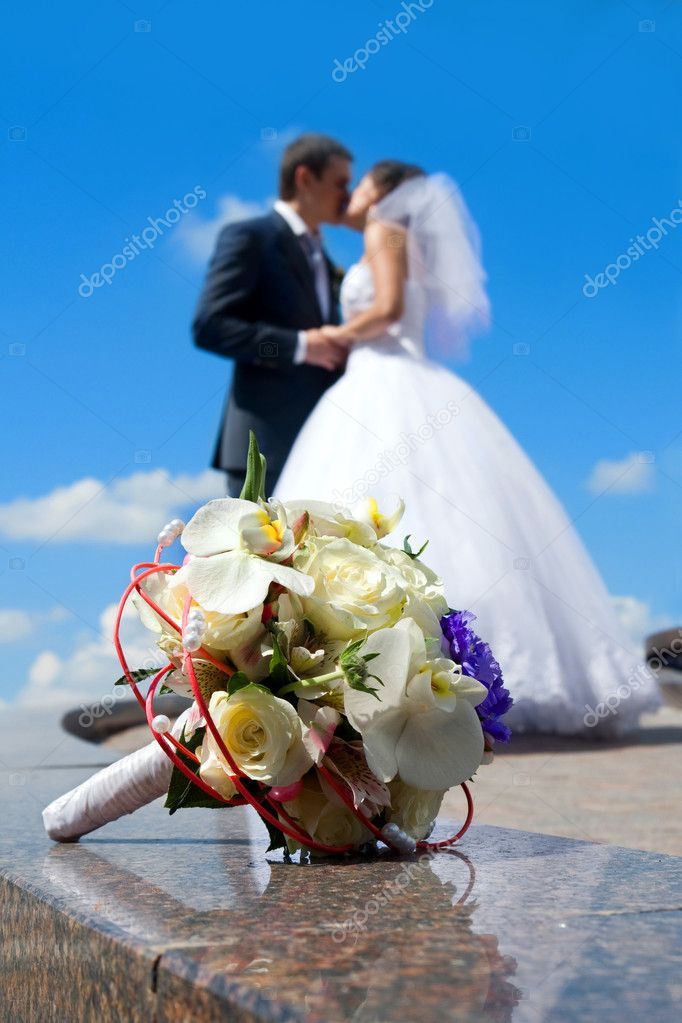 Bride's bouquet on the marble. Kissing couple on the background.  Stok fotoraf #1227730