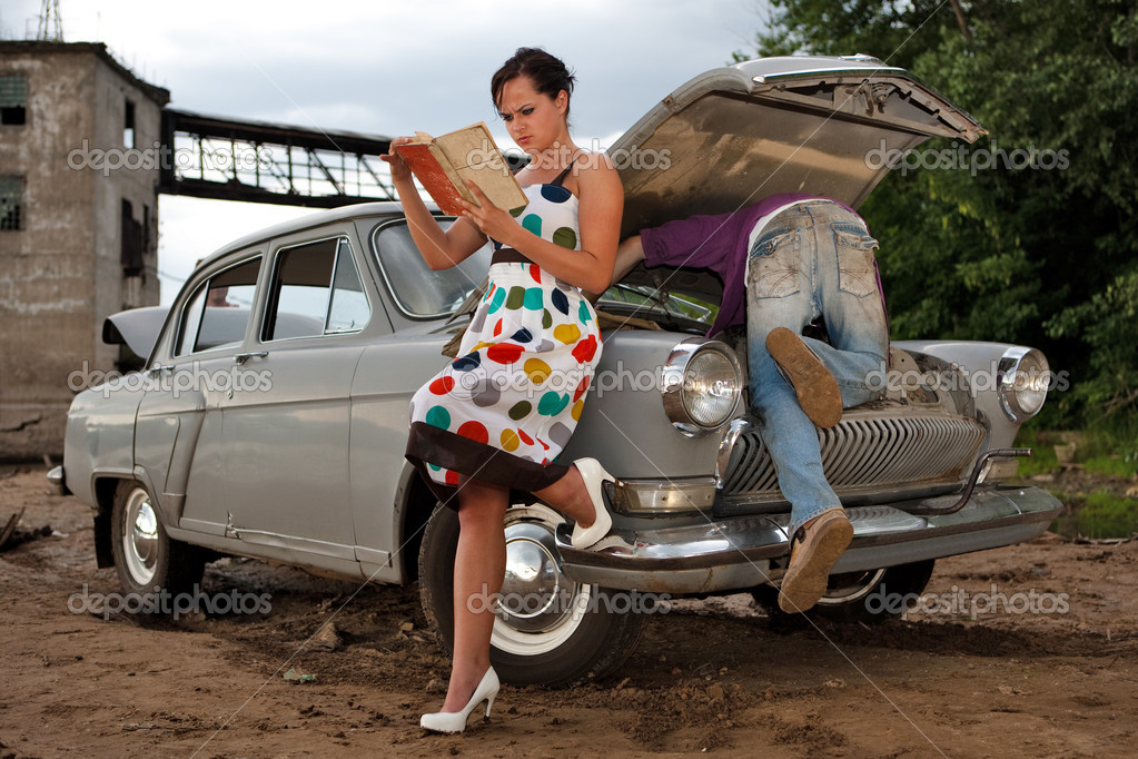 Pretty couple is trying to repair their old car using manual. Rural background.  Photo #1229010