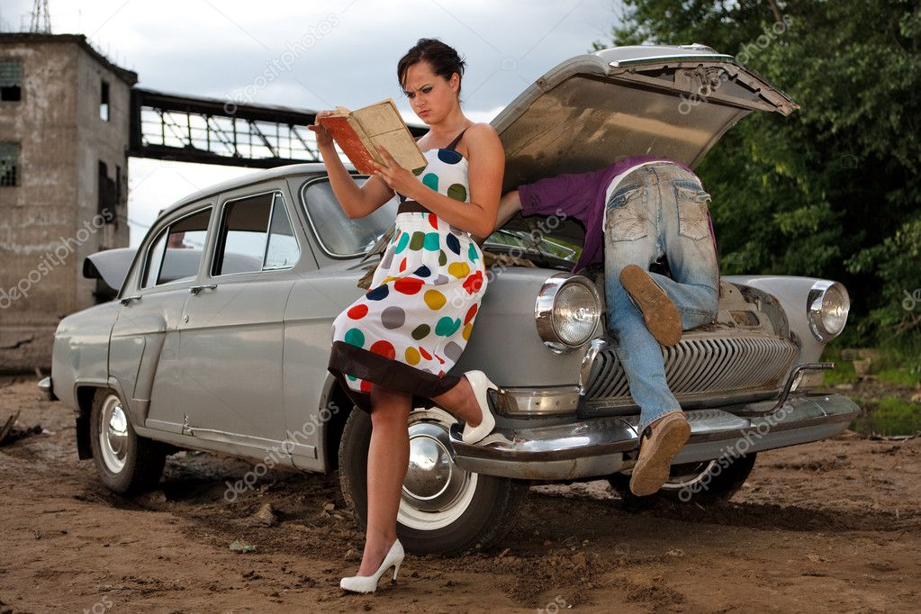 Pretty couple is trying to repair their old car using manual. Rural background. — Stock Photo #1229010