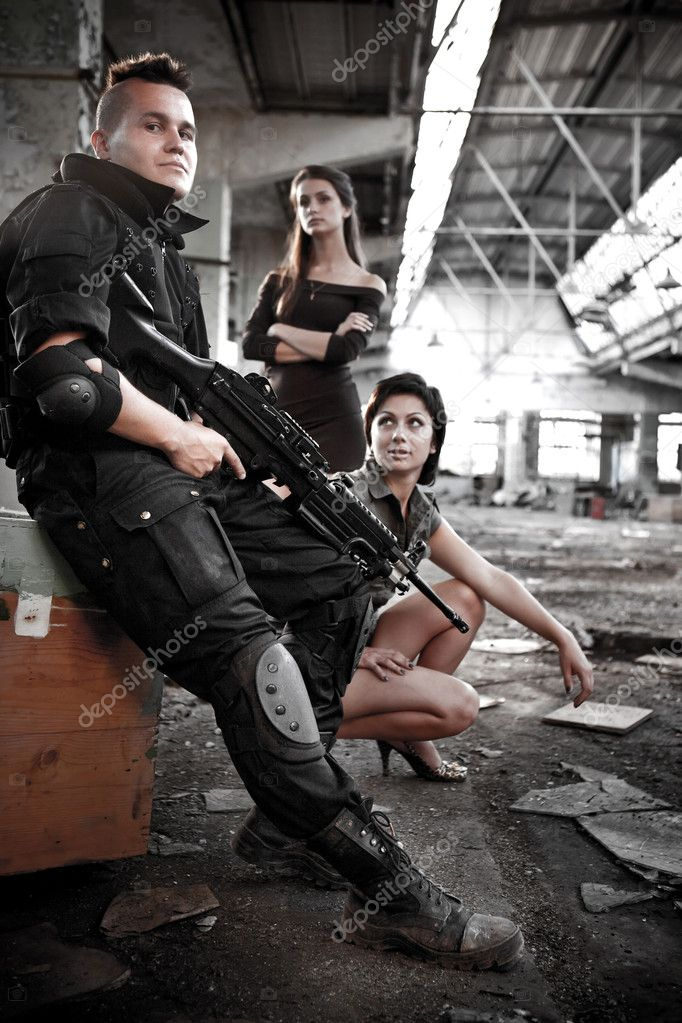 Armed mercenariy with machineguns and 2 pretty girls on the ruined building background. — Stock Photo #1229234