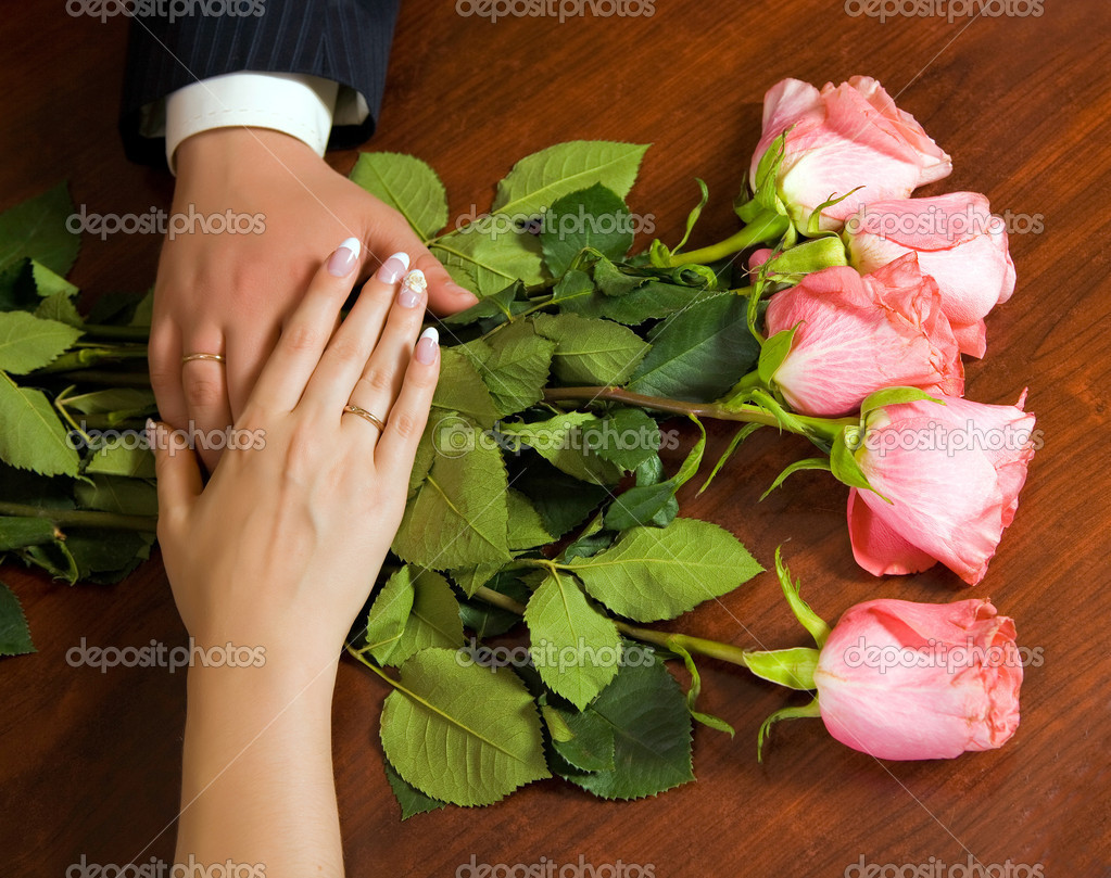 Hands with golden rings over the bouquet on the wooden background — Stock Photo #1229643