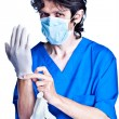 Surgeon struggle into gloves on hands - Stock Photo