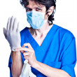 Stock Photo: Surgeon struggle into gloves on hands