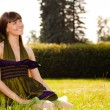 Pretty smiling girl is sitting on the gr — Stock Photo
