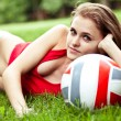 Girl lay on grass with volleyball ball - Stock Photo