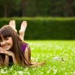 Pretty smiling girl is laying on green g — Stock Photo