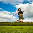 Pretty smiling girl is jumping on green — Stock Photo