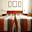 Hotel room interior with beds and frames — Stock Photo
