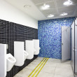 Public toilet with cubicles and urinals - Stock Photo