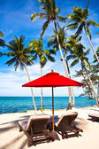 Red umbrella and chairs on sand beach in — Stock Photo