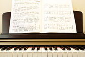 Piano and music paper — Stock Photo