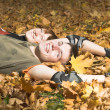 Couple lies on yellow leaves — Stock Photo #1329747