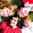 Four teenager lay on grass — Stock Photo