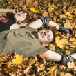 Couple lies on yellow leaves — Stock Photo #1329785