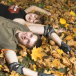 Couple lies on yellow leaves — Stock Photo