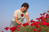 Good-looking girl on the poppies field — Stock fotografie