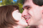 Happy kissing couple in the forest — Stock Photo