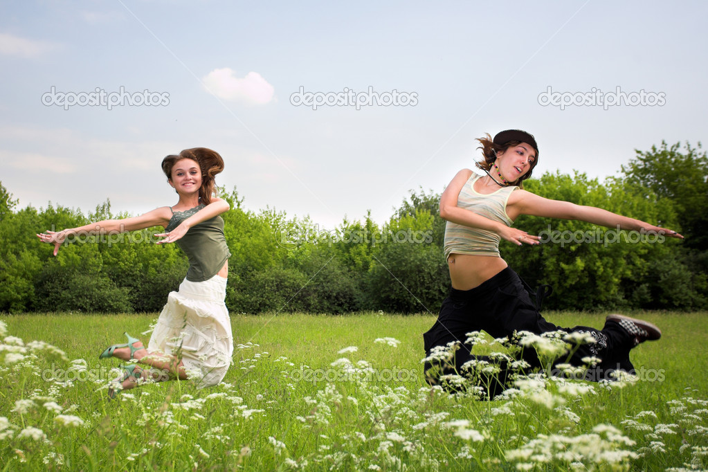 Two jumping girls on blue sky and green grass — Stock Photo #1329694