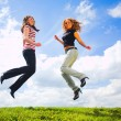 Two jumping girls on blue sky — Stock Photo