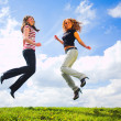 Two jumping girls on blue sky — Stock Photo #1331086