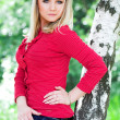 Dreaming girl in red near birch — Stockfoto