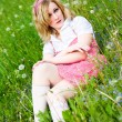 Blonde attractive girl sit on grass — Stock Photo