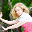 Blonde beautiful girl on tree — Stock Photo