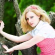 Blonde beautiful girl on tree - Stock Photo