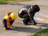 Sisters draw on asphalt — Stock Photo