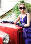 Girl in blue near red car — Stock Photo
