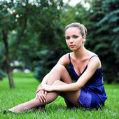 Teenager girl in blue sit on grass — Stock Photo