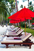 Red umbrellas and chairs — Stock Photo