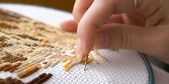 Woman's hand embroidering a picture (cross-stitch) — Stok fotoğraf
