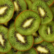 Green background slices kiwi — Stock Photo