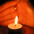 On a photo a candle near which brush of a hand in the form of the guard. A photo on a dark background. The photo is made in Ukraine — Stock Photo #1322518