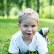 Little kid lie on green grass — Stock Photo #1203072