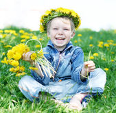 Happy kid with diadem and dandelions — Stock Photo