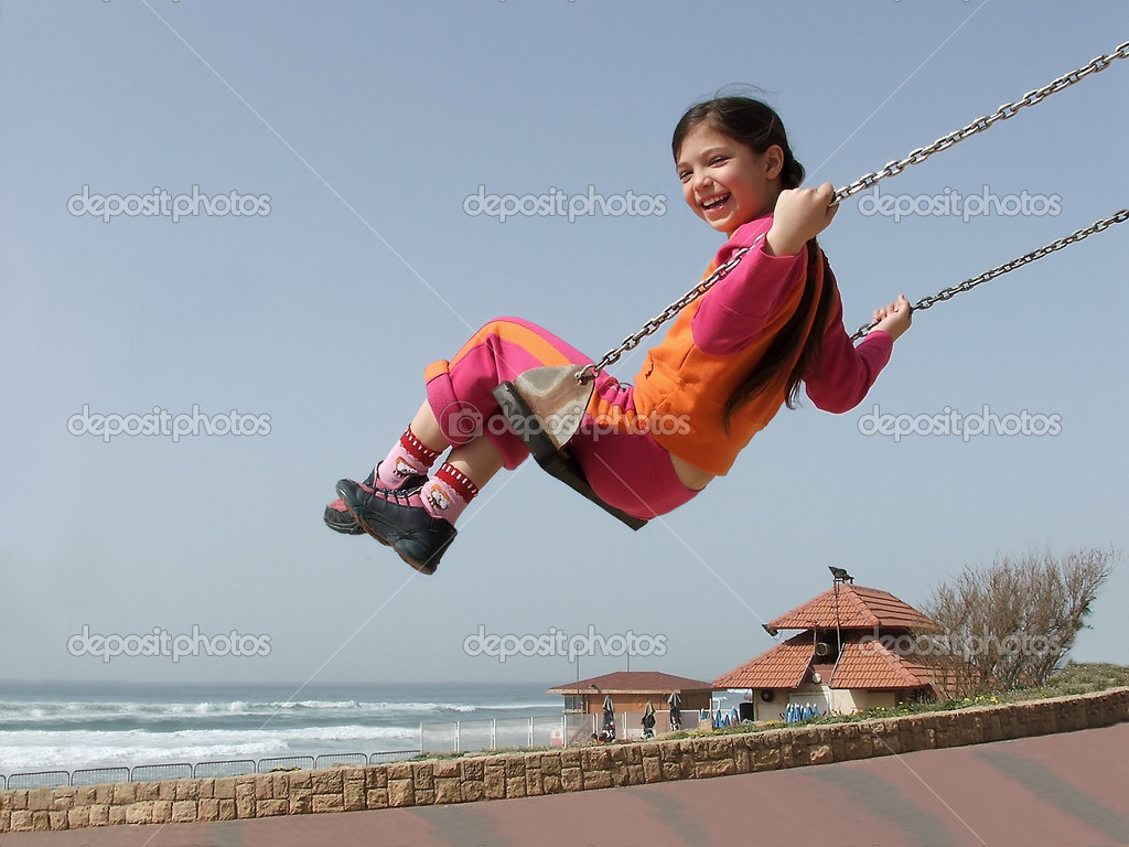 Smiling girl on swing against sky, sea beach in the background. — Stock Photo #2542459
