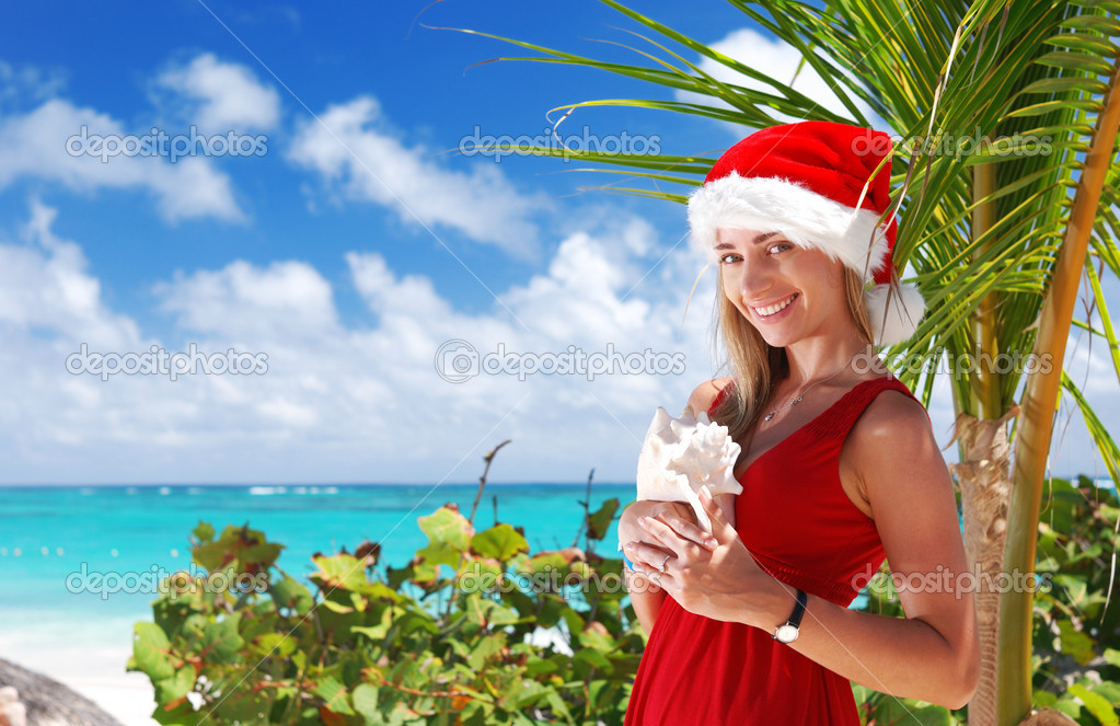 Woman on the beach in santa's hat — Stock Photo #1190411