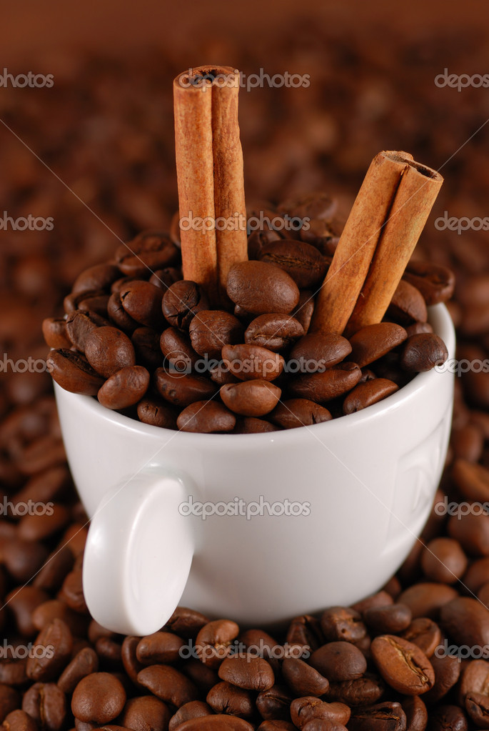 Coffee beans with cinnamon and white cup — Stock Photo #1200875
