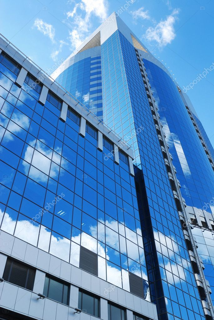 Modern office building with sky reflection in windows — Stock Photo #1234179